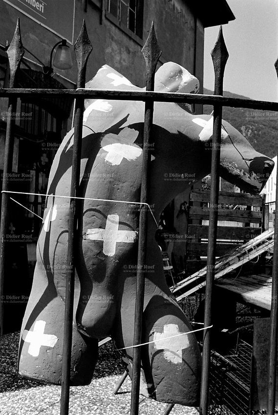 Switzerland. Canton Ticino. Bellinzona. Second hand shop. A manikin behind a fence with swiss flags painted on his body. A dummy used as a model or a replica of a human being. The flag of Switzerland consists of a red flag with a white cross (a bold, equilateral cross) in the centre. It is one of only two square sovereign-state flags. 1.08.2017  © 2017 Didier Ruef