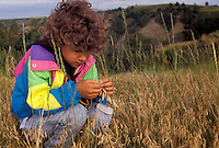AJ3537, girl, Theodore Roosevelt National Park, North Unit, North Dakota, Young girl (6 years old) squats down and observes a blade of prairie grass in her hands while hiking in Theodore Roosevelt National Park in the state of North Dakota.