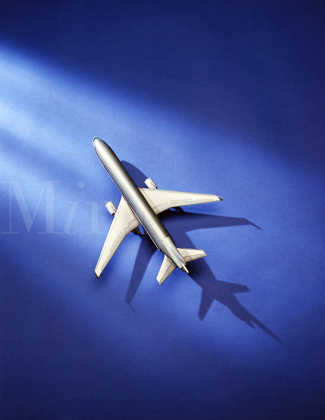 Toy airplane on blue surface with shadow.
