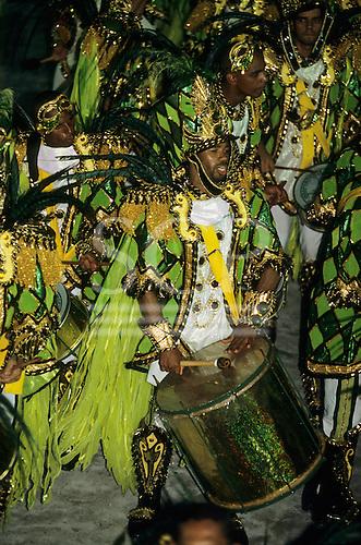 Rio de Janeiro, Brazil. Carnival: Mocidade samba school musicians in green and gold costumes playing surdo drums.