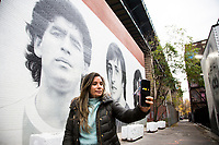 NEW YORK, UNITED STATES - NOVEMBER 25: A woman takes a picture in front of a mural of Diego Maradona's face  under the Manhattan Bridge on November 25, 2020. Argentine soccer legend Diego Maradona died at the age of 60, his spokesman announced on November 25 2020. (Photo by Pablo Monsalve/VIEWpress via Getty Images)