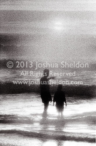 Parent & child at sunset looking out to sea<br />