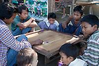 Myanmar, Burma. Bagan.  Young Men Playing a Board Game.