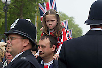 A girls who is not happy as she sits on her fathers shoulders as police stop her come down the mall to Buckingham Palace..Picture: Maurice McDonald/Universal News And Sport (Europe).29 April 2011..