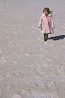Girl in pink coat on beach<br />