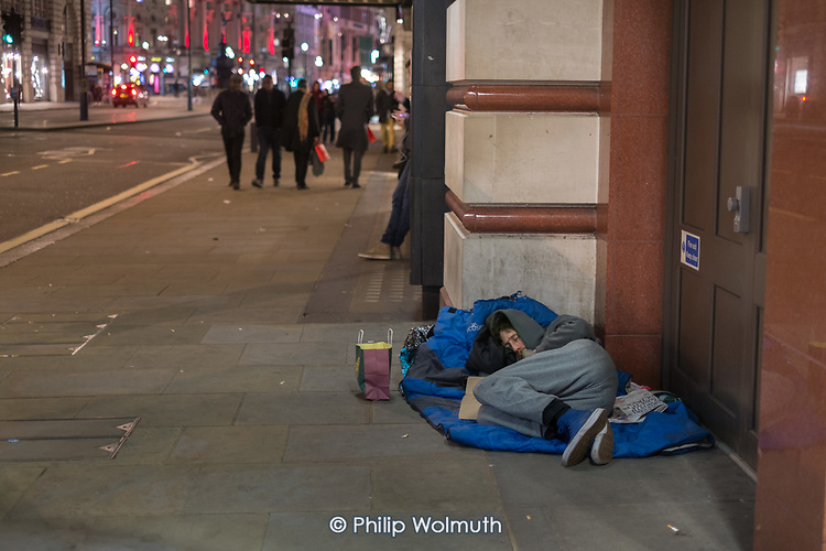 Young man sleeping in a doorway in Piccadilly, London
