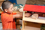 Education Preschool 3-5 year olds pretend play boy playing with small figures and doll house horizontal