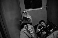 Travelers rest and sleep in a doorway between train cars in Gansu Province, China.
