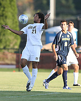 Justin Morrow #21 of the University of Notre Dame chests down the ball in front of Justin Meram #9 of the University of Michigan during a men's NCAA match at the new Alumni Stadium on September 1 2009 in South Bend, Indiana. Notre Dame won 5-0.
