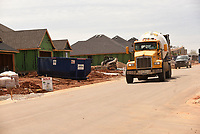 Construction traffic rolls March 30 2021 through Park View subdision in Lowell, being built by Riverwood Homes.<br />(NWA Democrat-Gazette/Flip Putthoff)