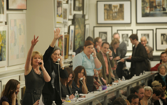 Surrounded by the Lehman Brothers Corporate Art Collection hanging from the walls, art buyers representatives signal the auctioneer their bids from a buyer on the end of a phone line or on the Internet during the Freeman's Gallery Auction House sale of former Lehman brothers artworks Sunday, November 1, 2009, in Philadelphia, Pa. (Bloomberg News/Bradley C Bower)