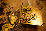 Parts of an antique clock are taken apart on the workbench as Florian Wullemann, watchmaker, repairs it in his boutique-workshop 'L'Horlogerie', Vence, France, 17 November 2010
