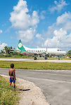 A local boy watches the flight arrive in Funafuti, Tuvalu. Flights to Funafuti are twice a week from Fiji.