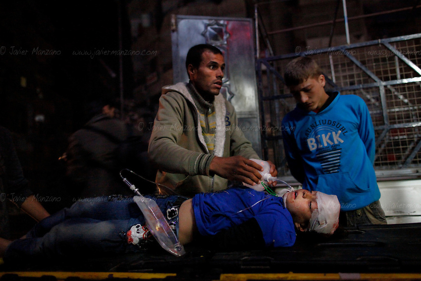 A man pumpos oxygen into the lungs of an 8-year-old girl who was fatally wounded by the shrapnel of a regime aircraft which fired its machine gun onto the vehicle the victims was traveling in along with her family.