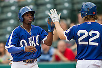 Oklahoma City Dodgers second baseman Darnell Sweeney (9) is greeted at home by teammate Kyle Jensen (22) during the Pacific Coast League baseball game against the Nashville Sounds on June 12, 2015 at Chickasaw Bricktown Ballpark in Oklahoma City, Oklahoma. The Dodgers defeated the Sounds 11-7. (Andrew Woolley/Four Seam Images)