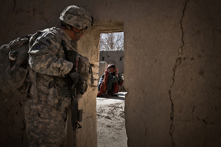 A medic with Charlie Co. 1st Battalion 12th Infantry Regiment, 4th Infantry Division keeps an eye on a man suspected of being a Taliban fighter during a patrol in Zhari District, Kandahar, Afghanistan. The violently contested district sits astride the strategically Highway 1 ringroad between Kandahar and Lashkar Gah and is seen by some as the birthplace of the Taliban movement.