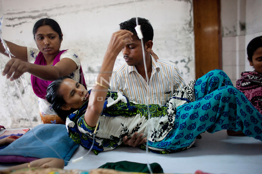 Workers of Tuba garments are now suffering from the consequences of the hunger. They are being helped with  intravenous saline drips inside the garments factory. Dhaka, Bangladesh