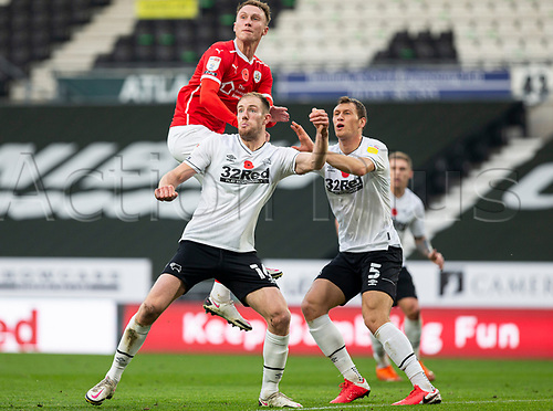 7th November 2020; Pride Park, Derby, East Midlands; English Football League Championship Football, Derby County versus Barnsley; Cauley Woodrow of Barnsley leaps above Matthew Clarke of Derby County to head the ball in the Derby goal area watched by Krystian Bielik of Derby County