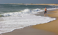 A young boy plays in the waves on Cape Hatteras beach in the North Carolina Outer Banks. ..Has model release