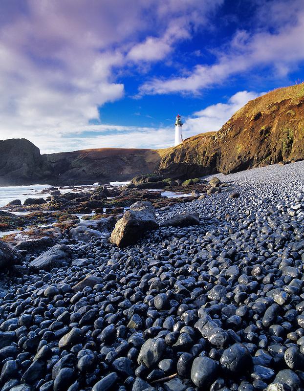 Yaquina Lighthouse with black beach rocks. Oregon.