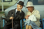 Seniors husband and wife whispering together in conversation. Smartly dressed old couple at Cannes South of France. 1980