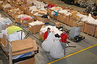 """Pictured: Staff members, Jonathan Beasley and Jo Williams pictured amongst the box pallets full of wedding dresses on offer at John Pye Auctions in Pyle, south Wales, UK.<br /> Re: A bride cried tears of joy after her missing wedding dress was found among a pile of 20,000 gowns in a warehouse.<br /> Meg Stamp, 27, paid £1,300 for the beautiful ivory lace dress but it  was seized by liquidators after a bridal company went bust.<br /> It was boxed up along with 20,000 others and due to be sold for a knock-down price at auction.<br /> But determined Meg banged on the auctioneer door saying: """"I want my dress back"""".<br /> Staff at John Pye auctioneers in Port Talbot spent three hours sifting through boxes until they finally found Meg's dream dress."""