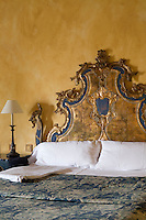 An ornate bed with a gold-leaf and painted headboard in a guest room at the Hacienda Benazuza, Sanlucar La Mayor, Spain
