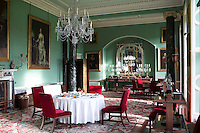 Inside the house on the Clandeboye estate, which is the home to Lady Dufferin, Marchioness of Dufferin and Ava. The green dining room with a sideboard laden with candelabra.