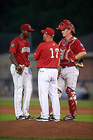 Auburn Doubledays pitching coach Tim Redding (17) talks with pitcher McKenzie Mills (14) and catcher Erik VanMeetren (13) during a game against the State College Spikes on July 6, 2015 at Falcon Park in Auburn, New York.  State College defeated Auburn 9-7.  (Mike Janes/Four Seam Images)