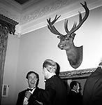 The Quantock Staghounds. A mounted stags head looks down on the revellers who have spilled out of the hunt ball marquee and into Bagborough House. West Bagborough, Somerset...