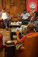 Cuba, Havana.  Partagas Cigar Factory.  Patrons Conversing in the Lounge.