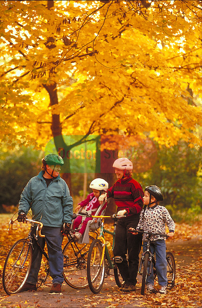 family bicycling amidst fall foliage