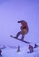 A snowboarder takes a flying leap amid falling snow on the slopes of Mauna Kea on the Big Island of Hawaii.