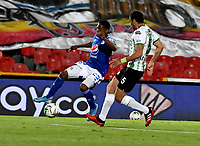 BOGOTA - COLOMBIA, 31-10-2020: Emerson Rodriguez de Millonarios F. C. y Diego Braghieri de Atletico Nacional disputan el balon, durante partido entre Millonarios F. C. y Atletico Nacional de la fecha 17 por la Liga BetPlay DIMAYOR 2020 jugado en el estadio Nemesio Camacho El Campin de la ciudad de Bogota. / Emerson Rodriguez of Millonarios F. C. and Diego Braghieri of Atletico Nacional figth for the ball, during a match between Millonarios F. C. and Atletico Nacional of the 17th date for the BetPlay DIMAYOR League 2020 played at the Nemesio Camacho El Campin Stadium in Bogota city. / Photo: VizzorImage / Luis Ramirez / Staff.