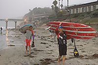 Tom Jones (R) and Teddy Casil prepare to enter the water on their paddle boards at La Jolla Shores, California near Scripps Institution of Oceanography early on Saturday, November 3 2007.  Tom is set to become the first person to paddle the length of the California coast when his journey ends on Sunday at the Mexican border.  He hopes that his achievement will draw attention to the large amount plastic pollution in the oceans.   Tom trained for his endeavor with Laird Hamilton and Teddy on Maui.  Teddy was joining Tom for the last two legs of the trip.