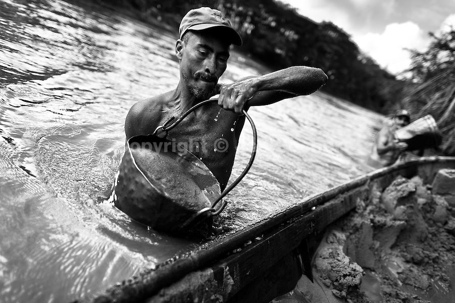 A Colombian sand miner unloads a bucket full of sand into his boat anchored in the middle of the river La Vieja in Cartago, Colombia, 10 December 2013. Artisanal (unmechanised) sand mining is an ancient mining technique used to obtain sand for construction purposes. Depending on the natural conditions (strength of the stream, depth of the river etc.), together with the sand miners' physical condition, the material is extracted in metal buckets, either by standing on the river bottom and searching for sand by feet, or, diving up to 3-5 meters deep using a wooden plank with steps. In spite of the physically demanding work, a sand miner's daily salary does not exceed 15-20 US dollars. However, the sand miners are very proud of their profession, valuing their work freedom above all, and usually, as long as their health and strength permit, they keep facing the river stream.