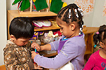 Education Preschool boy and girl playing together in pretend play area