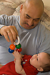 3 month old baby boy with father, held, interested in toy father dangles for him, older father in early 50s Hispanic Puerto Rican