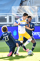 KANSAS CITY, KS - NOVEMBER 22: Carlos Fierro #21 San Jose Earthquakes tackled by Gianluca Busio #27 and Gerso Fernandes #12 of Sporting Kansas City during a game between San Jose Earthquakes and Sporting Kansas City at Children's Mercy Park on November 22, 2020 in Kansas City, Kansas.