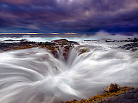 Standing at the edge of a large blowhole on the Big Island's shoreline during sunset as Violent waves erupt and streak back through the cracks of a large blowhole along Keahole Point coastline, Big Island.