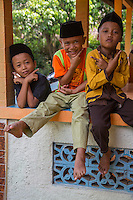 "Borobudur, Java, Indonesia.  Indonesian Gestures.  Young Boys waiting for Friday Noon Prayers at Neighborhood Mosque.  Crossing the wrists near the face means ""keep smiling."" (boys on left and right).  Holding the thumb up and the index finger extended straight means ""keep smiling.""  (boy in the middle)"