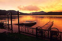 USA, New York, Lake Placid, Adirondack State Park, motor boat moored at pier at dawn.