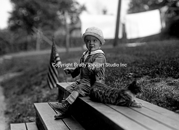 Wilkinsburg PA:  Brady Stewart Jr smoking a toy pipe and playing with the neighbor's cat.