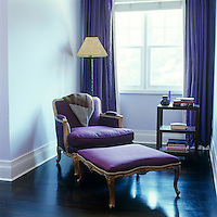 A gilded armchair and footstool upholstered in an up-to-the-minute deep violet strike a regal note in this living room