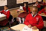 K-8 Parochial School Bronx New York Grade 4 children sitting in rows listening in class and following reading in handout horizontal