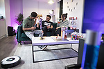 """© Joel Goodman - 07973 332324 - all rights reserved . 12/01/2020 . Salford , UK . Lounge of the rented flat of KAYNE LEWIS (25 - left) , which he shares with CHASE (the 5 month old Chihuahua - 2nd left) and some fish , in apartment block """"Duet"""" , on Salford Quays in Greater Manchester . Also pictured on the sofa sharing wine and snacks in front of the television are Kayne's friends CAMERON INCE (22) and BEATRIX DEXTER (25 - right) . Photo credit : Joel Goodman"""