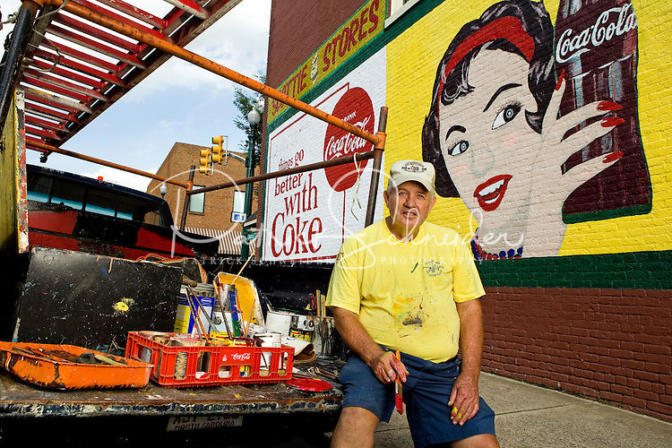 Seventy-two-old Coca-Cola mural painter Andy Thompson, has painted thousands of murals in his 54-years  of working for Coca-Cola. Thompson who started as a painter is now a restorer of the iconic wall murals and advertisements. Thompson was doing some touch-up work on the mural in downtown, Concord, NC.<br /> <br /> Photo by: PatrickSchneiderPhoto,com