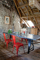 Vintage Tolix chairs surround a metal table by Axel-Olivier Icard in the open plan kitchen/dining area