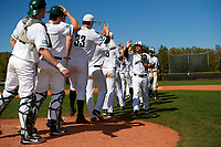 Dartmouth Big Green Hayden Rappoport (20) high fives teammates after a game against the Villanova Wildcats on March 3, 2018 at North Charlotte Regional Park in Port Charlotte, Florida.  Dartmouth defeated Villanova 12-7.  (Mike Janes/Four Seam Images)