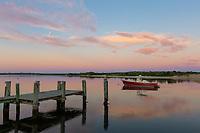A lone red boat is moored on Menemsha Creek under a colorful pre-sunrise sky in Chilmark, Massachusetts on Martha's Vineyard.